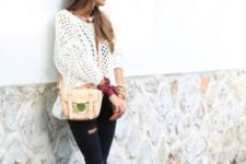 With white sweater, pastel colored bag and navy blue jeans