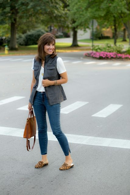 With white t-shirt, gray vest, crop jeans and brown bag