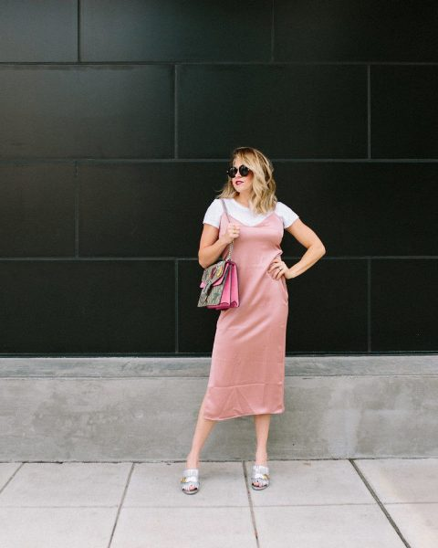 With white t-shirt, printed bag and pale pink midi dress