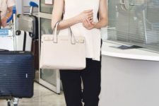 With white top, beige bag and straight pants