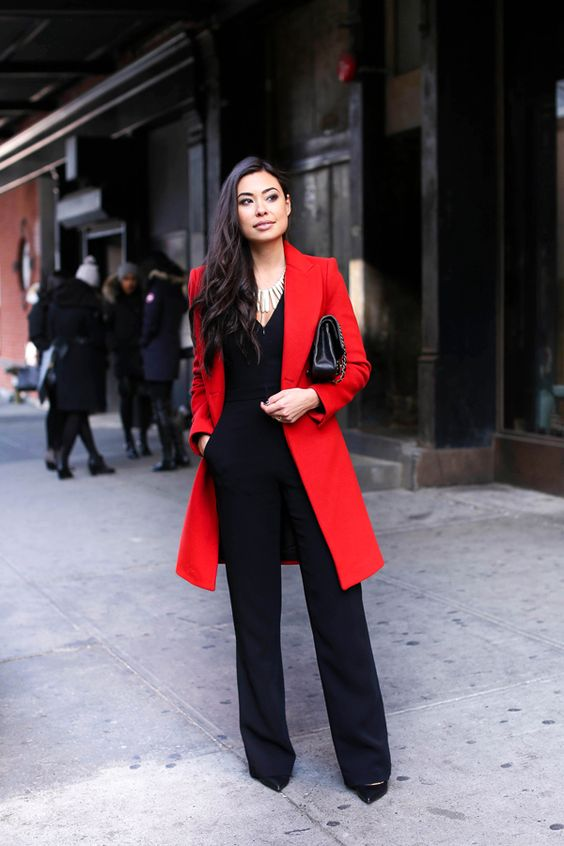 a black jumpsuit paired with a red coat, black heels and a clutch for work