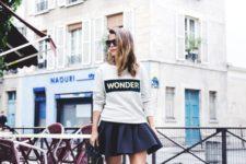 02 a black skater mini skirt, a grey printed sweatshirt, black flat shoes and a bag