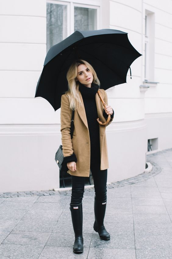 a black sweater, black leather pants, black rubber boots, a short camel coat for rainy days