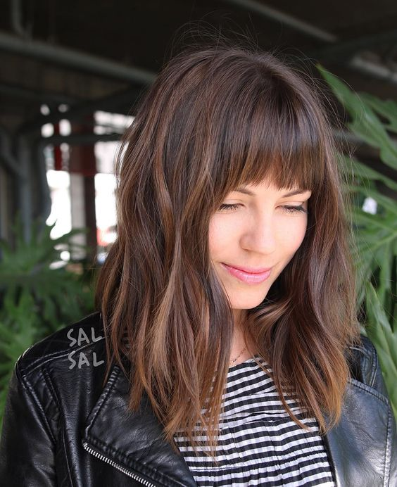 a layered brunette A-line lob with fringe bangs and highlights is a great cut for someone seeking versatility
