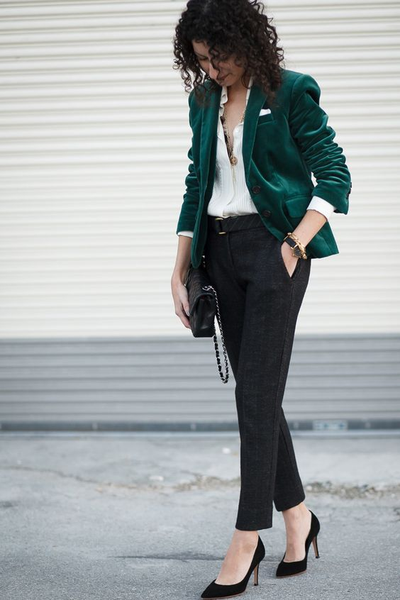 a work outfit with dark grey pants, a white shirt, an emerald velvet blazer and black heels