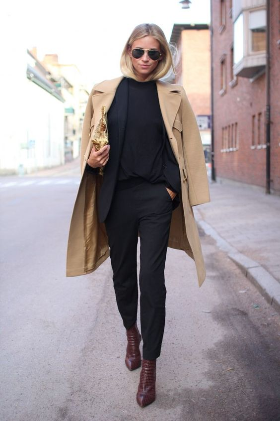 a navy pantsuit, a black top, burgundy boots and a camel coat for a bold work look