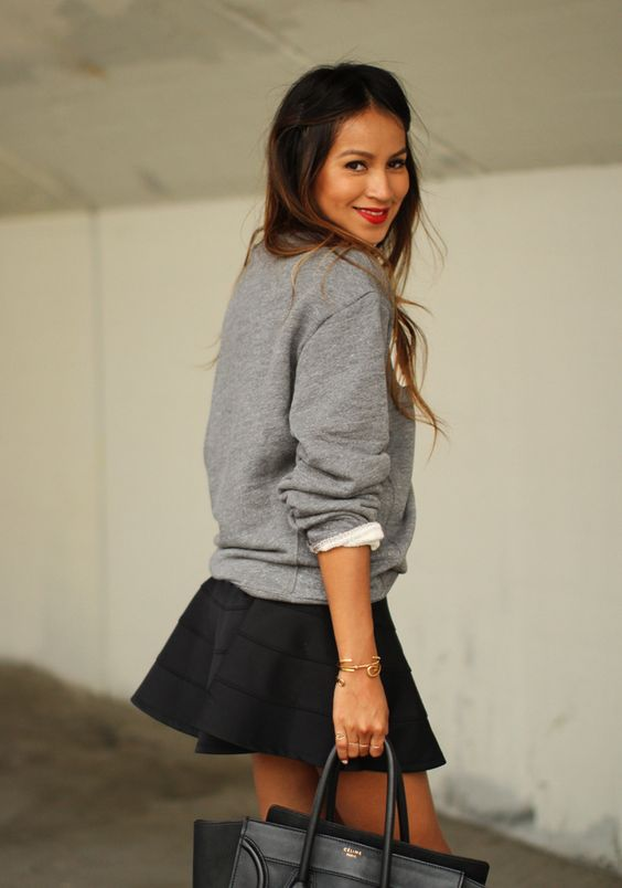 a grey printed sweatshirt, a black skate skirt, a black bag for a sporty feel