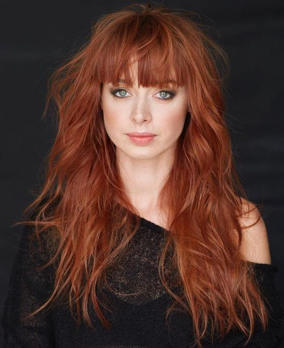 a long layered copper haircut with bangs and a texture to make a statement