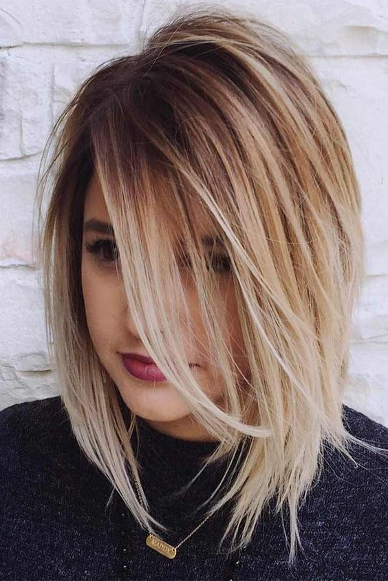 a medium length bob with much texture and a dark root for a trendy look