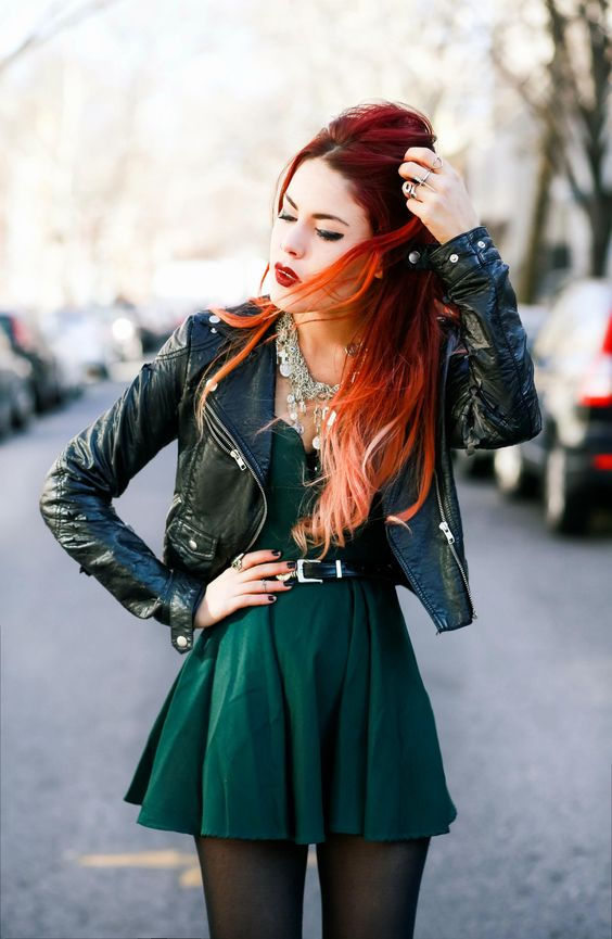 an emerald mini dress with a belt, a dark green cropped leather jacket and a statement necklace