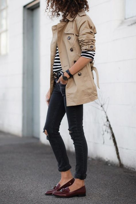 black ripped jeans, burgundy moccasins, a striped long sleeve top and a tan short trench