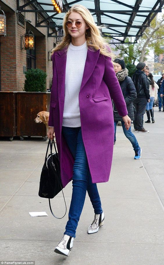 Gigi Hadid wearing a white sweater, blue skinnies, printed booties and a black bag