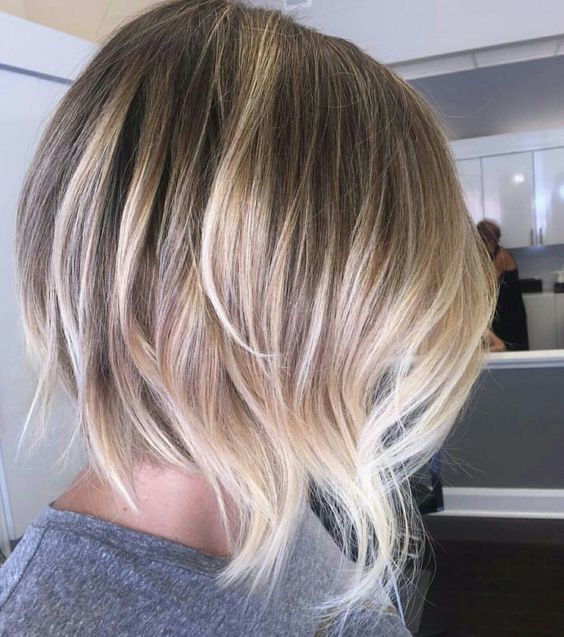 a dark root, blonde to silver balayage on a shaggy haircut for a bold look