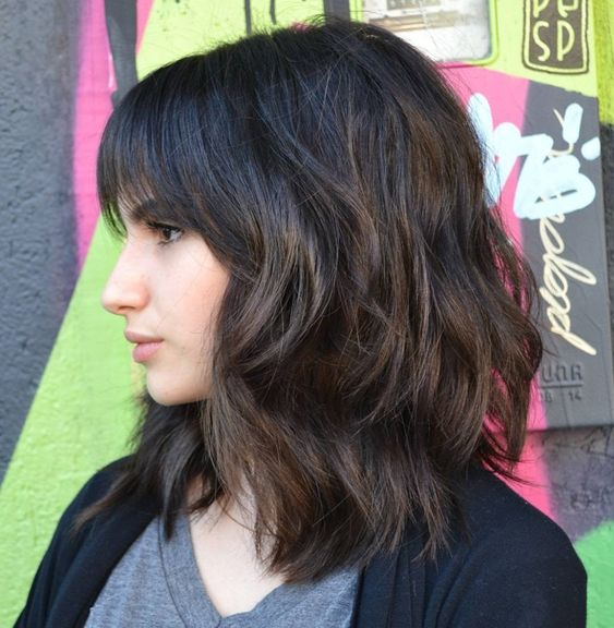 a medium length haircut with bangs and much dimension is a modenr option