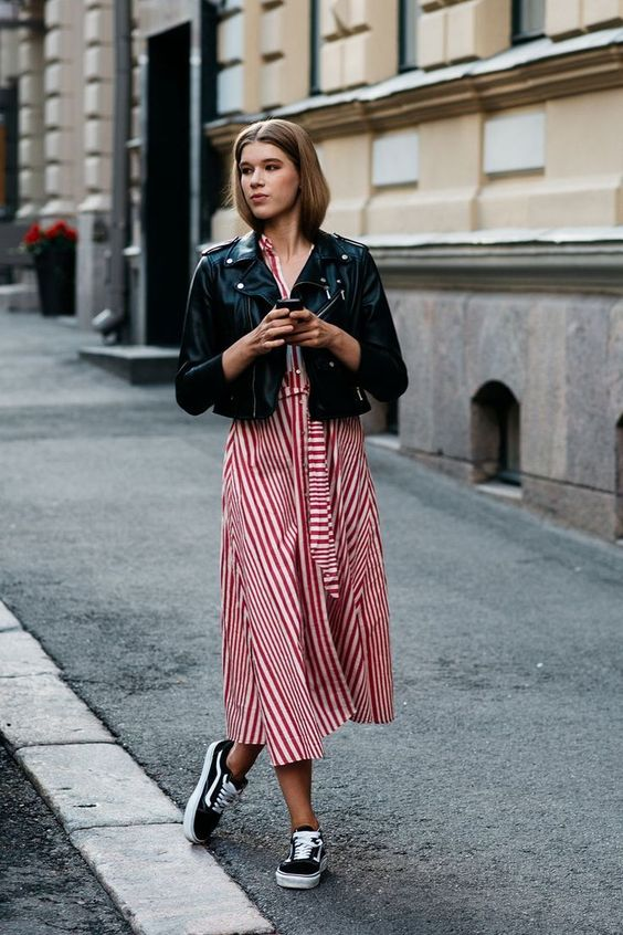 a striped red and white midi dress, a black cropped jacket, black Vans sneakers