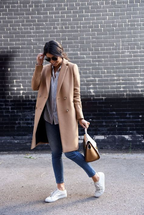 blue jeans, a striped shirt, white sneakers, a tan bag and a camel coat