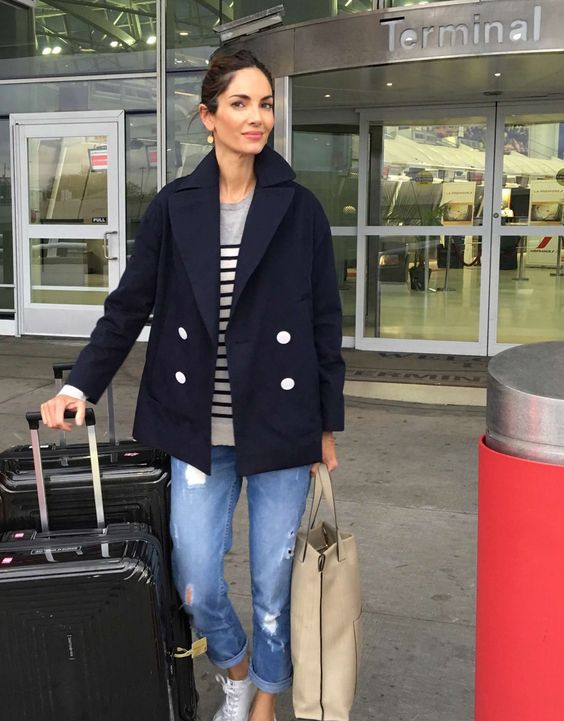 distressed jeans, white sneakers, a striped top, a navy short coat for comfy travelling