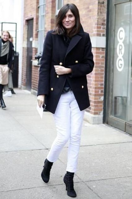 a black top, black boots, white jeans and a navy short coat for a contrast