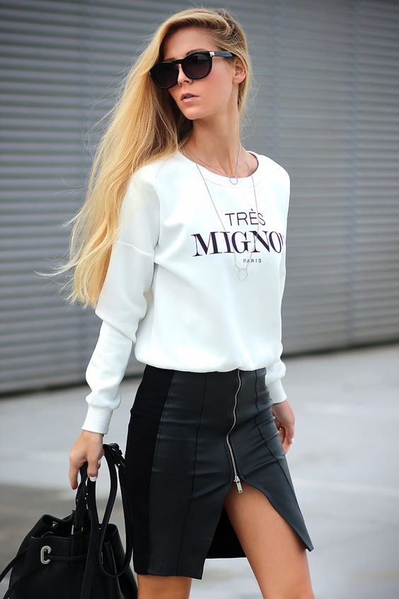 a white printed sweatshirt, a black mini skirt with a slit and a black bag for a sexy feel