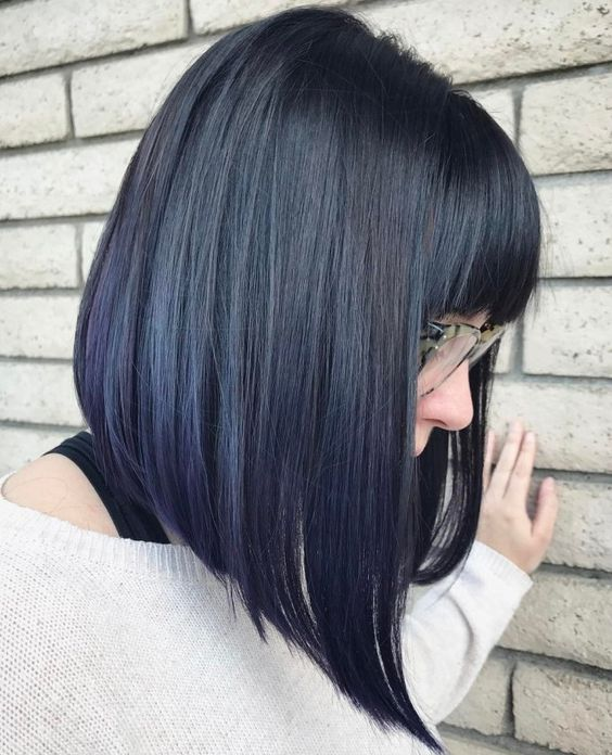 an angled bob with bangs is styled straight to highlight the angles