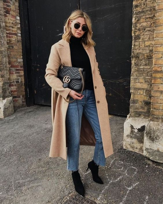 a black turtleneck, ablue denim, black booties, a midi camel coat and a black bag