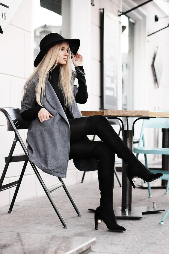 a black turtleneck, black leggings, tall boots and a hat plus a short grey woolen coat