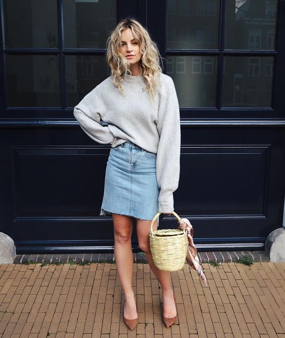 a grey oversized sweatshirt, a blue denim skirt, brown shoes and a basket as a bag