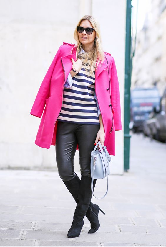 a striped top, black leather pants, black boots, a hot pink coat as a bold touch