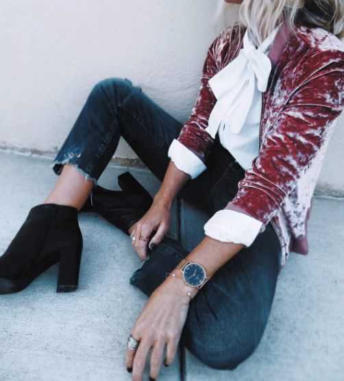 black jeans with a raw hem, black booties, a white bow shirt, a pink crushed velvet blazer