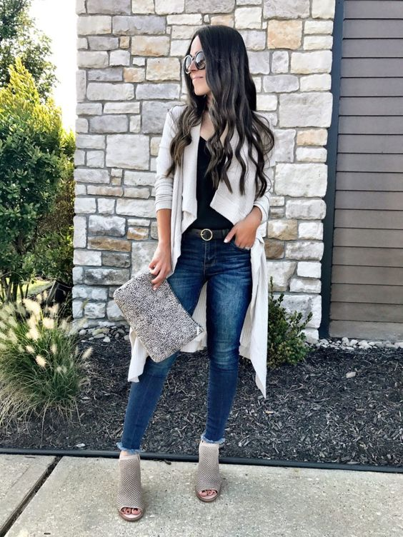 blue jeans, a black top, an off-white cardigan and booties plus a matching clutch