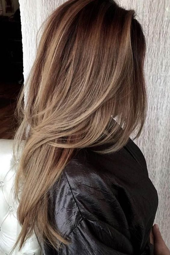 a chic long layered haircut with balayage and a darker root for highlighting the layers
