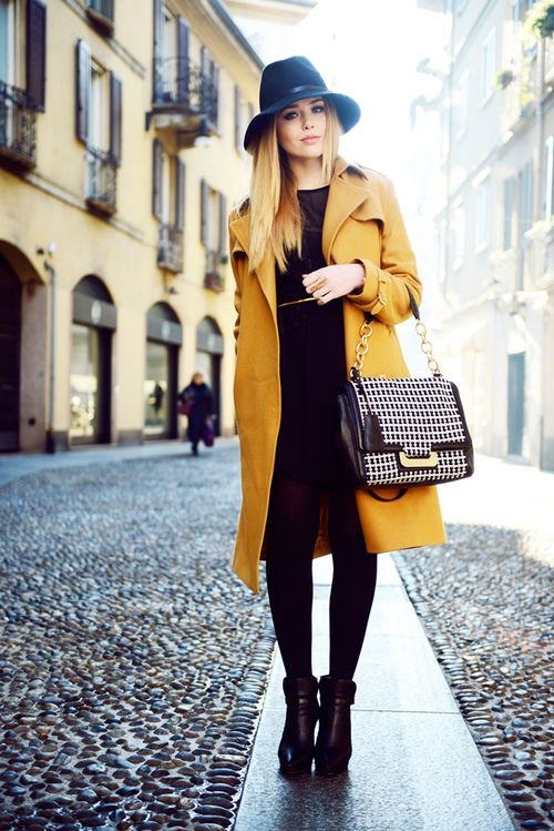 a total black look with a dress and heels and a mustard coat as a colorful touch