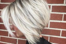 10 a chic blonde layered bob with a dark root for depth and a touch of drama