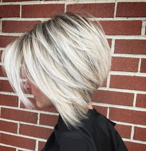 a chic blonde layered bob with a dark root for depth and a touch of drama