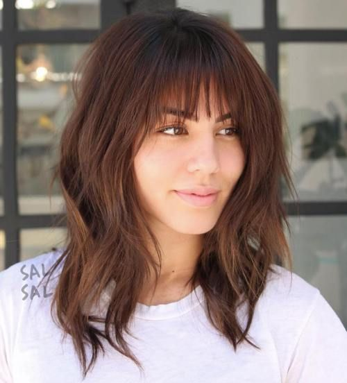 a layered long bob with a fringe and a bit of grunge for a bold look