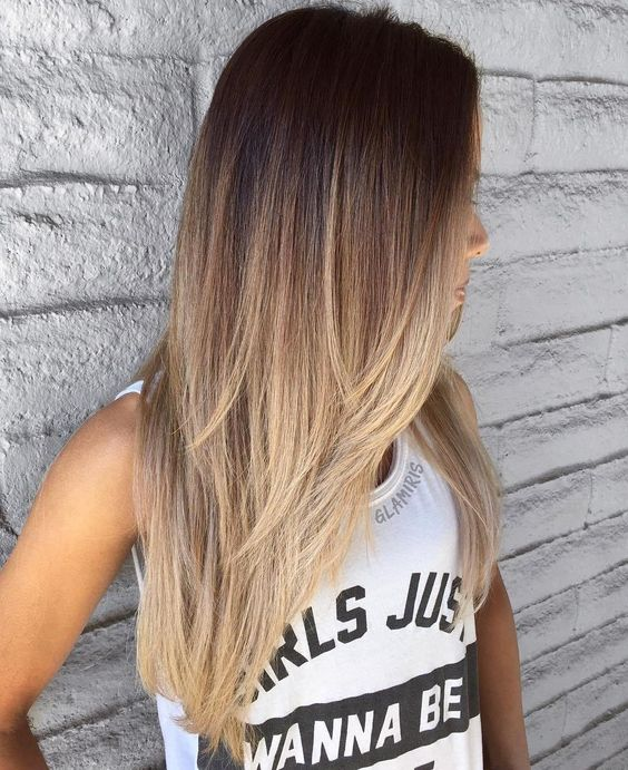 a long cascading layered haircut with a brown to blonde ombre to make a statement