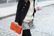 10 black booties, a printed mini skirt, an oversized creamy sweater, a black short coat and an orange clutch
