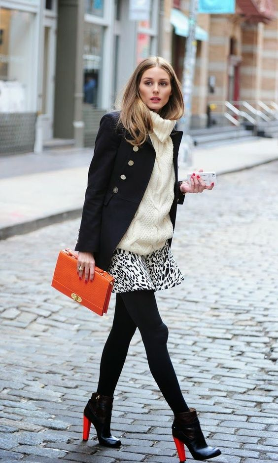 black booties, a printed mini skirt, an oversized creamy sweater, a black short coat and an orange clutch
