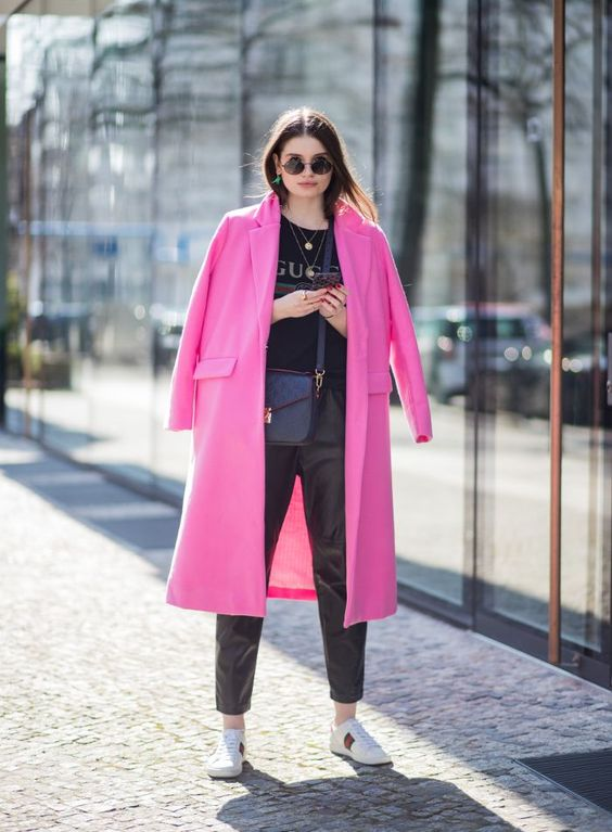 white sneakers, black leather pants, a printed tee and a hot pink midi coat