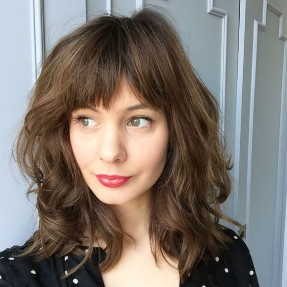 a medium length haircut with a straight bang is a chic and girlish idea