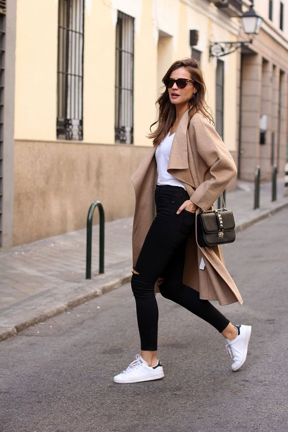 black ripped jeans, white sneakers, a white top and a long camel coat plus a black bag
