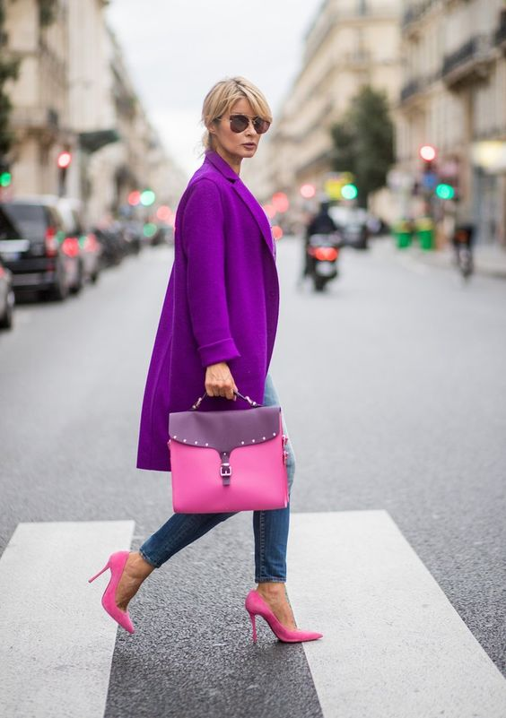 a bright purple coat, pink shoes and a bag and blue skinnies