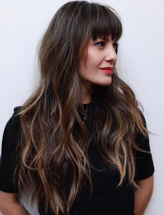 a long layered haircut with balayage and eyebrow-skimming bangs for an effortless look
