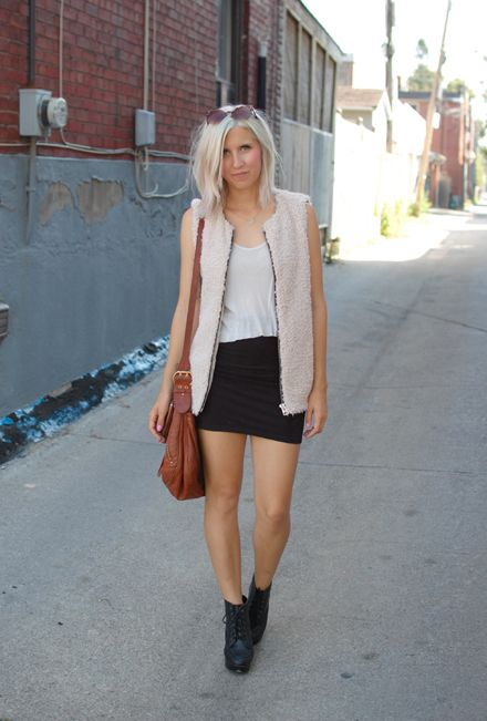 a black mini, a white tee, black booties, a blush faux fur vest and a brown bag