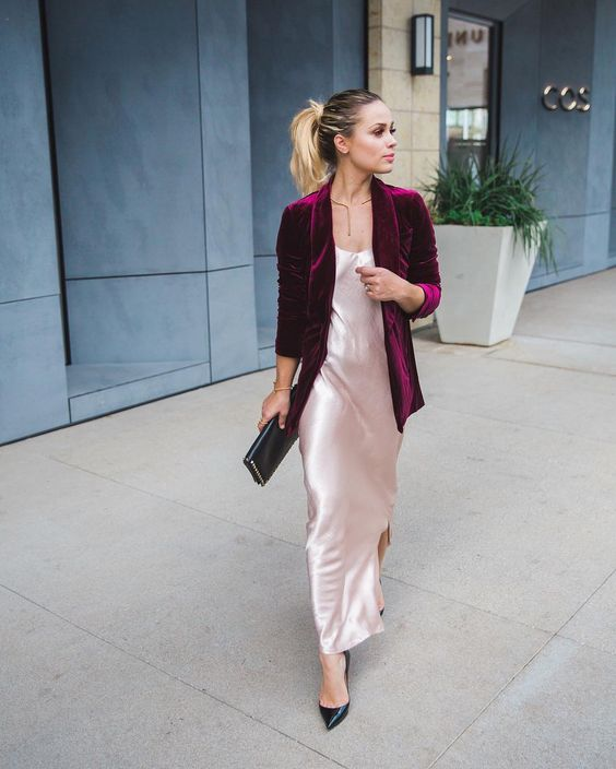 a blush silk slip dress with a side slit, a plum-colored velvet blazer and black shoes