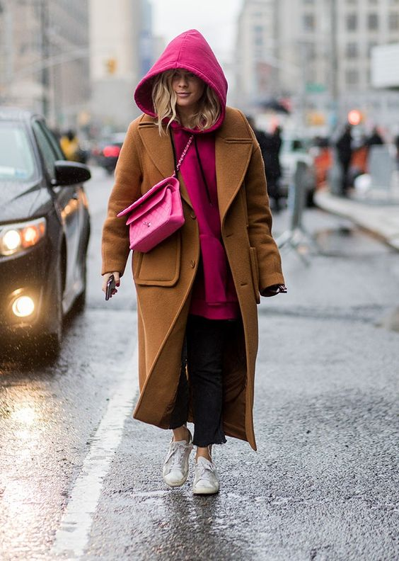 a mustard coat, white sneakers, a bright pink hoodie and bag for a casual yet bold look