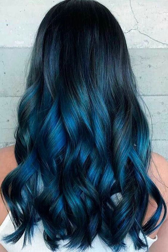 long black hair highlighted with indigo into teal balayage and with chic waves