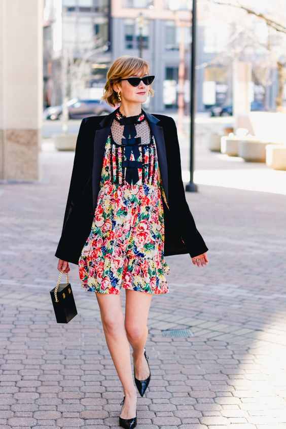 a colorful floral mini dress, a black velvet blazer, black shoes and a bag