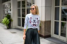 14 a printed sweatshirt, a dark green pleated midi skirt, black booties and a green bag