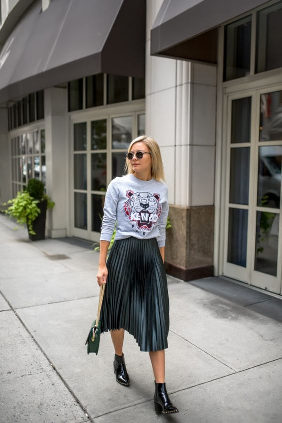 a printed sweatshirt, a dark green pleated midi skirt, black booties and a green bag